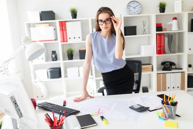 Bella ragazza in ufficio è in piedi vicino al tavolo e ripara gli occhiali con la mano.