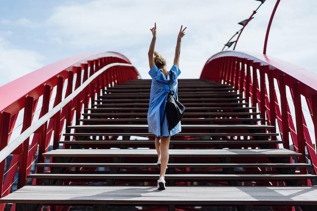 Bella ragazza in un abito blu in posa sul ponte