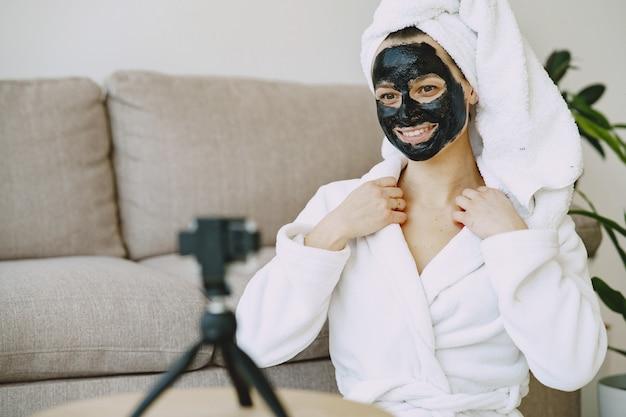 Bella ragazza in un accappatoio bianco a casa che registra un video