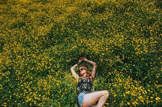 Bella ragazza in un campo di fiori gialli