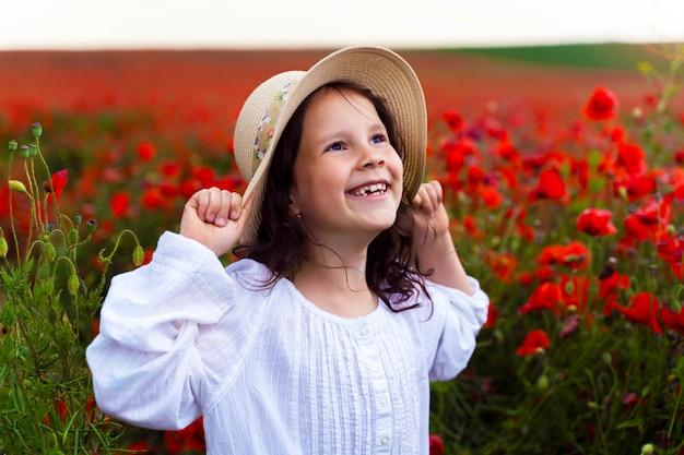 Bella ragazza in un cappello di paglia in un campo con papaveri