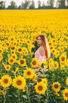 Bella ragazza in un enorme campo giallo di girasoli.
