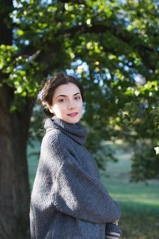 Bella ragazza in un maglione in un parco in autunno