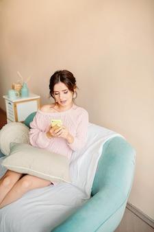 Bella ragazza in un maglione lavorato a maglia tiene il telefono in mano e sorride