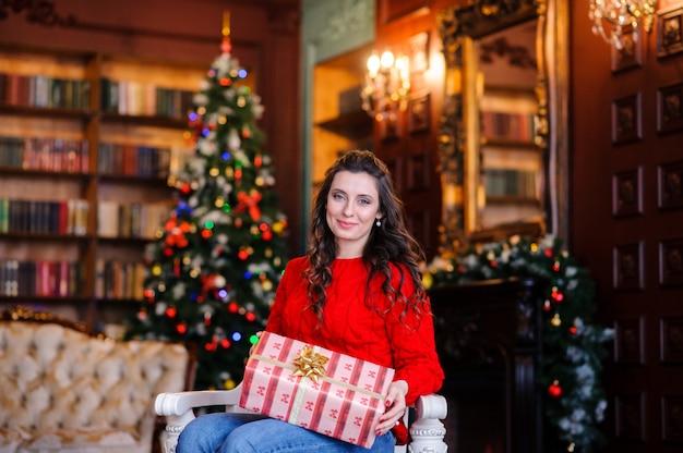 Bella ragazza in un maglione rosso vicino all'albero di natale.