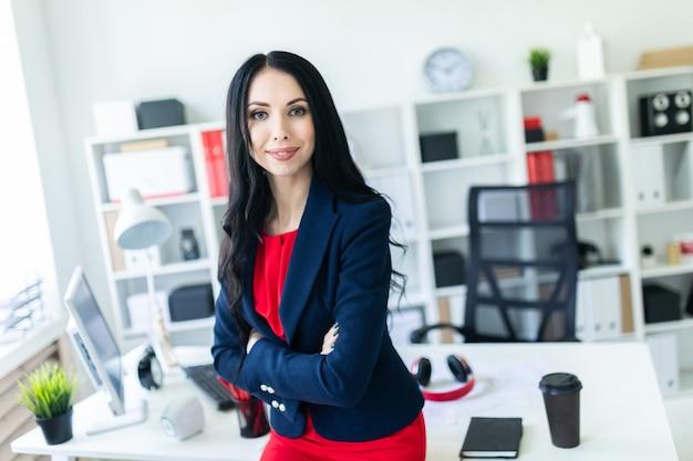 Bella ragazza in un tailleur è in piedi in ufficio, appoggiandosi su un tavolo.