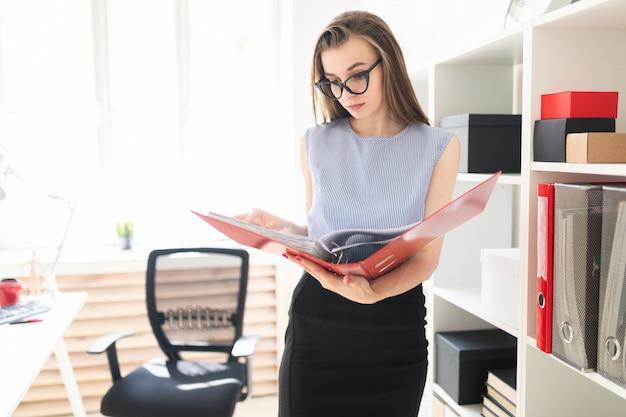Bella ragazza in un ufficio si trova vicino a un rack e scorre attraverso una cartella con documenti.