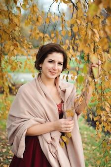Bella ragazza in un vestito rosso nella foresta di autunno