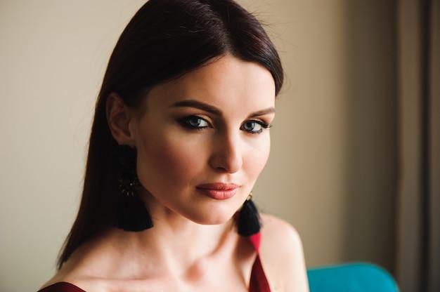 Bella ragazza in un vestito rosso seduto vicino alla finestra