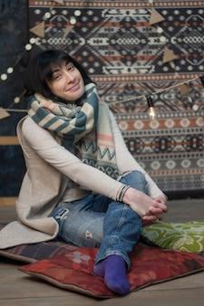 Bella ragazza in una sciarpa calda sullo sfondo di un interno scandinavo minimalista e ghirlande, natale e capodanno, messa a fuoco selettiva