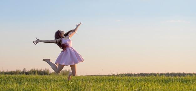 Bella ragazza in vestito rosa che salta nel campo
