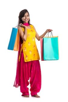 Bella ragazza indiana che tiene e che posa con i sacchetti della spesa su uno spazio bianco