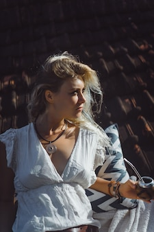 Bella ragazza indiana del hippie con capelli biondi lunghi sul tetto che beve il tè del compagno.