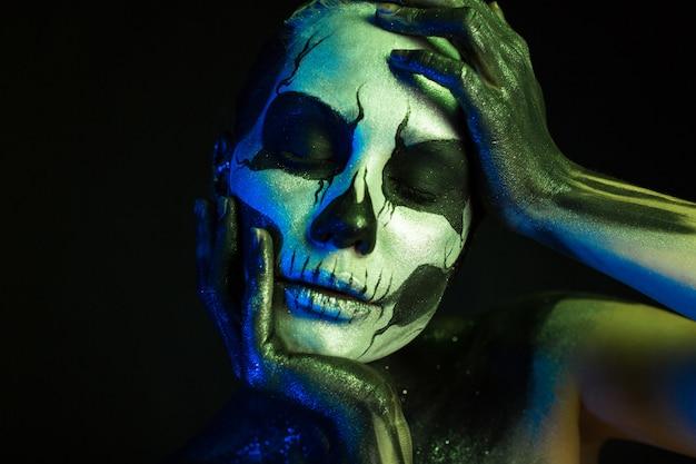 Bella ragazza inquietante con il trucco scheletro
