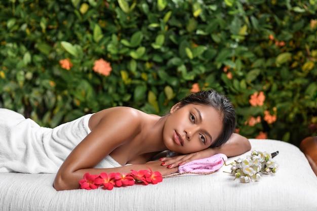 Bella ragazza interrazziale si trova su un lettino da massaggio con rametti di fiori