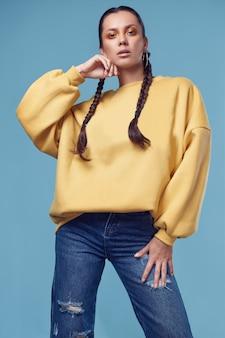Bella ragazza ispanica affascinante in jeans e felpa con cappuccio gialla