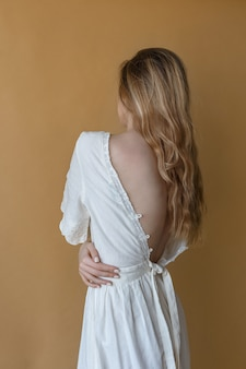 Bella ragazza magra con capelli lunghi in abito bianco con schiena nuda in posa su sfondo beige