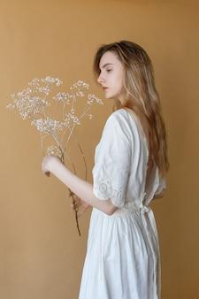 Bella ragazza magra con i capelli lunghi in abito bianco con schiena nuda in posa su sfondo beige e con fiori bianchi tra le mani