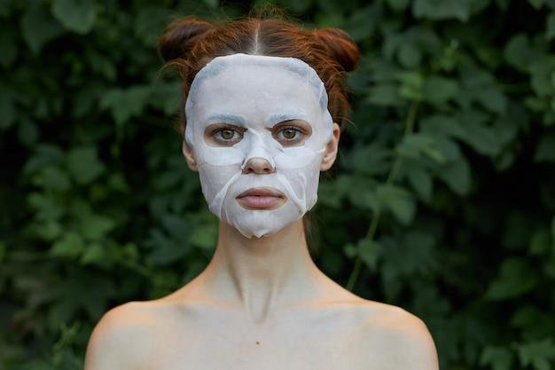 Bella ragazza maschera bianca cura della pelle foglie verdi