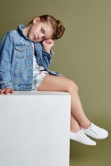 Bella ragazza meditabonda che si siede su un cubo bianco e che posa, modelli della scuola