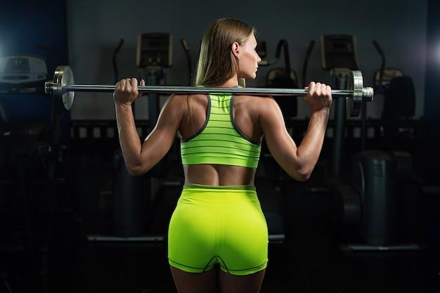 Bella ragazza muscolare atletica sexy. ragazza fitness si allena in palestra, facendo esercizi con un bilanciere