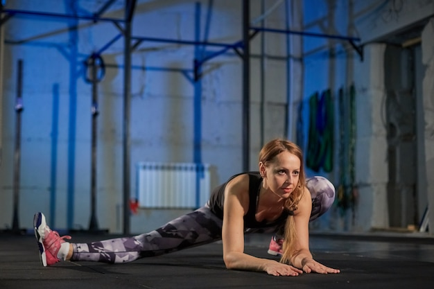 Bella ragazza muscolare in ghette grigie facendo stretching. palazzetto dello sport in stile industriale