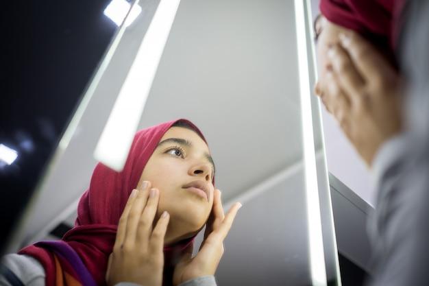Bella ragazza musulmana che esamina specchio che controlla la pelle del fronte