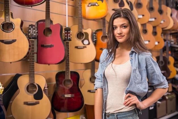 Bella ragazza nel negozio di musica con chitarre spagnole