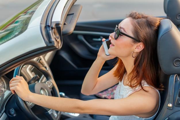 Bella ragazza nell'automobile cabrio convertibile in una giornata di sole in una città