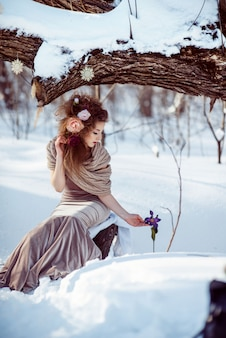 Bella ragazza nella foresta invernale