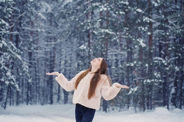 Bella ragazza nella foresta nevosa di inverno