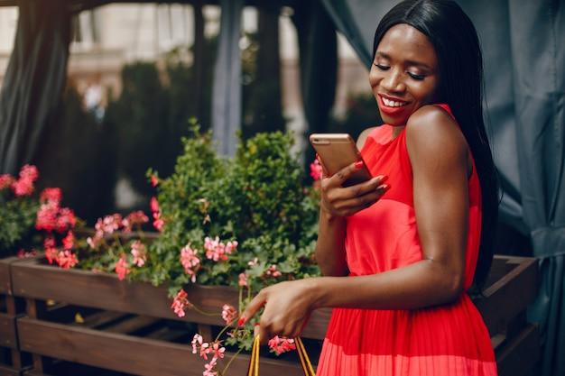 Bella ragazza nera con i sacchetti della spesa in una città