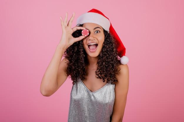 Bella ragazza nera con il chip di poker del casinò che porta il cappello e il vestito di santa di festa