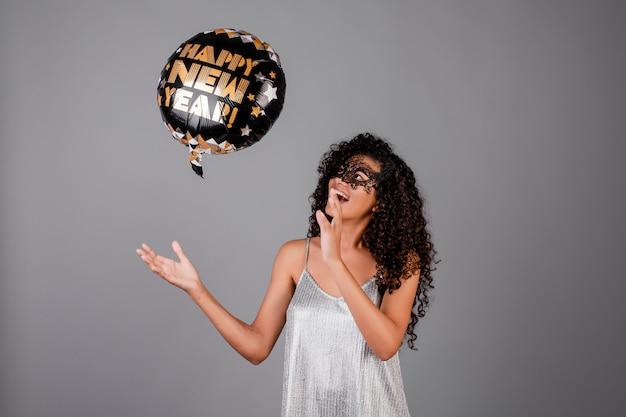 Bella ragazza nera con la maschera da portare di travestimento del pallone del buon anno isolata sopra grey