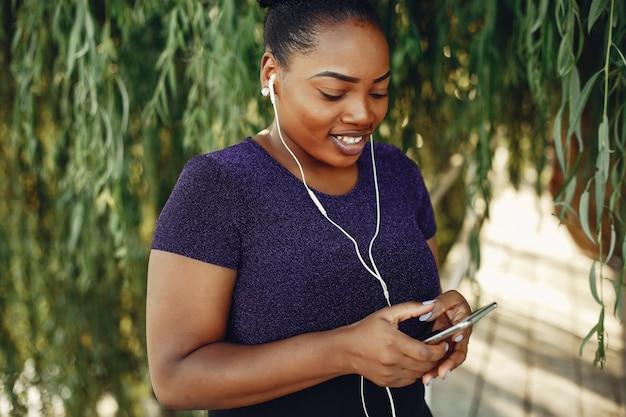 Bella ragazza nera in piedi in un parco di sumer