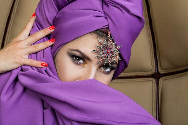 Bella ragazza orientale in un turbante di acai con bigiotteria su una fronte