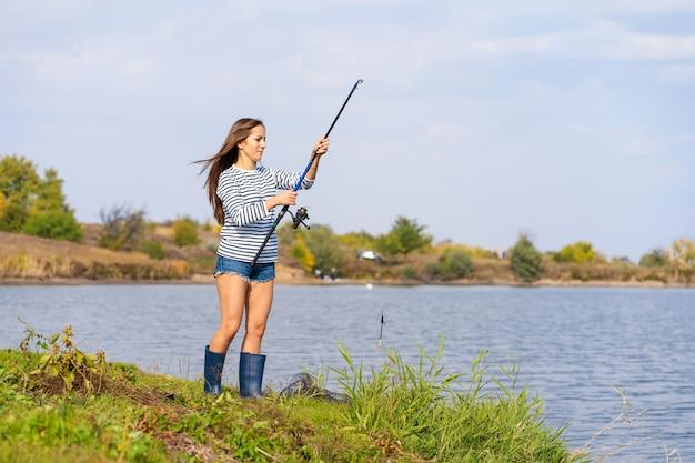 Bella ragazza pesci sul lago.