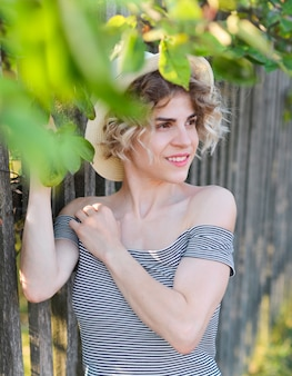 Bella ragazza positiva con capelli ricci in un cappello in piedi sulla natura tra gli alberi verdi nelle foglie