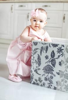 Bella ragazza prende i giocattoli dalla scatola. vestito rosa.