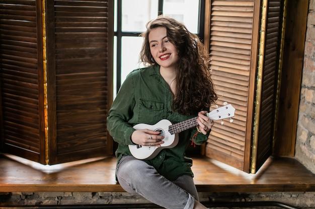 Bella ragazza riccia che si siede sul davanzale della finestra in appartamento loft, suonando strumento musicale ukulele bianco e cantando canzoni
