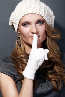 Bella ragazza riccia in cappello e guanti bianchi