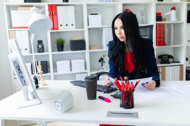 Bella ragazza riempie i documenti, seduto in ufficio al tavolo.