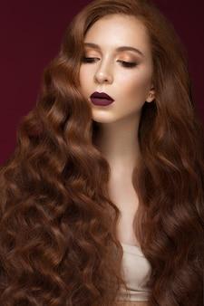 Bella ragazza rossa con i capelli perfettamente ricci e il trucco classico. volto di bellezza.