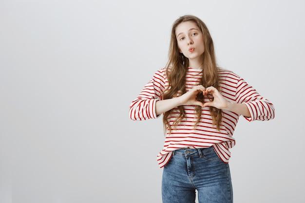 Bella ragazza sciocca che mostra il gesto del cuore, mostrando amore e cura