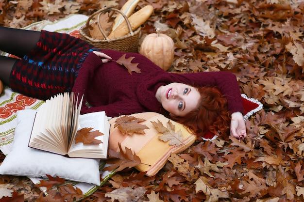 Bella ragazza sdraiata sui fogli di autunno