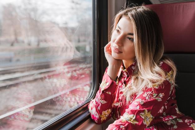 Bella ragazza seduta da sola in un treno e guarda tristemente fuori dalla finestra