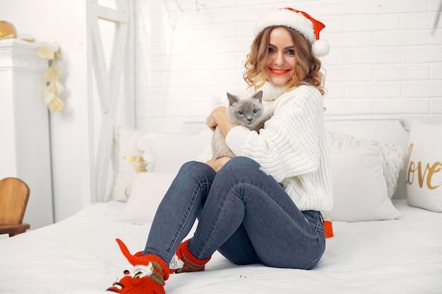 Bella ragazza seduta su un letto con gattino carino