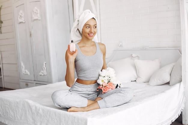 Bella ragazza seduta su un letto con prodotti di bellezza