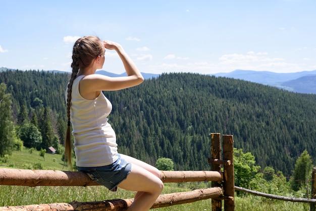 Bella ragazza seduta su una staccionata di legno e guarda in lontananza sullo sfondo di montagne verdi