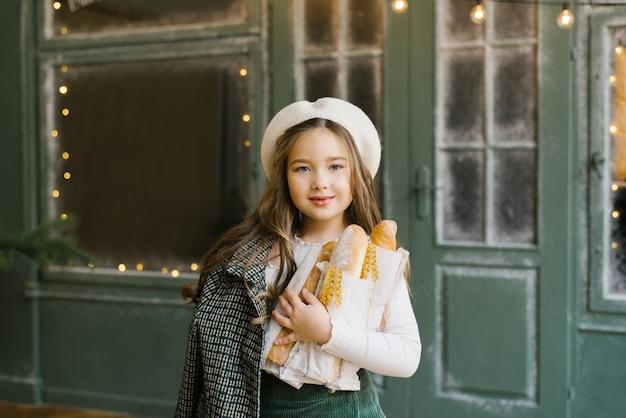Bella ragazza senza denti di sei anni sorridente in un berretto bianco che tiene le borse delle baguette
